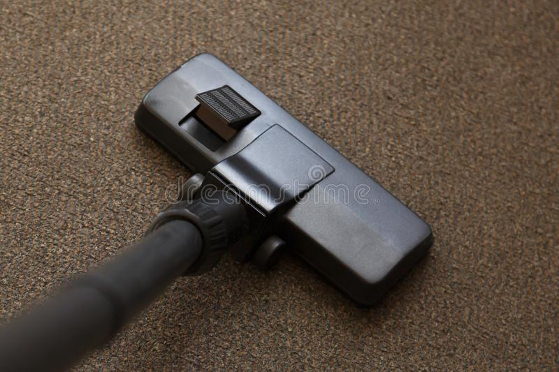 Close-up of the head of a modern vacuum cleaner. Vacuum cleaner grey carpet. A close-up of the head of a modern vacuum cleaner is used while vacuuming a thick stock image