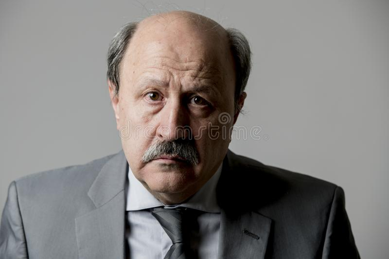 Close up head portrait of bald 60s senior business man sad and depressed looking desperate and feeling low in sadness emotion royalty free stock photos