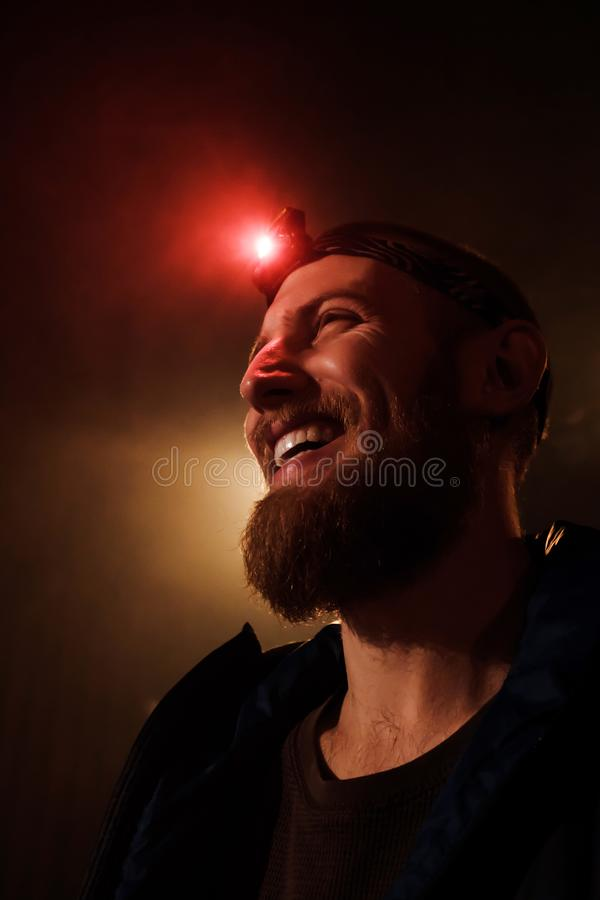 Close-up head-shot of young bearded extreme man with red head lamp on forehead. Close-up headshot of a brave young  bearded man with a red head light on his stock images