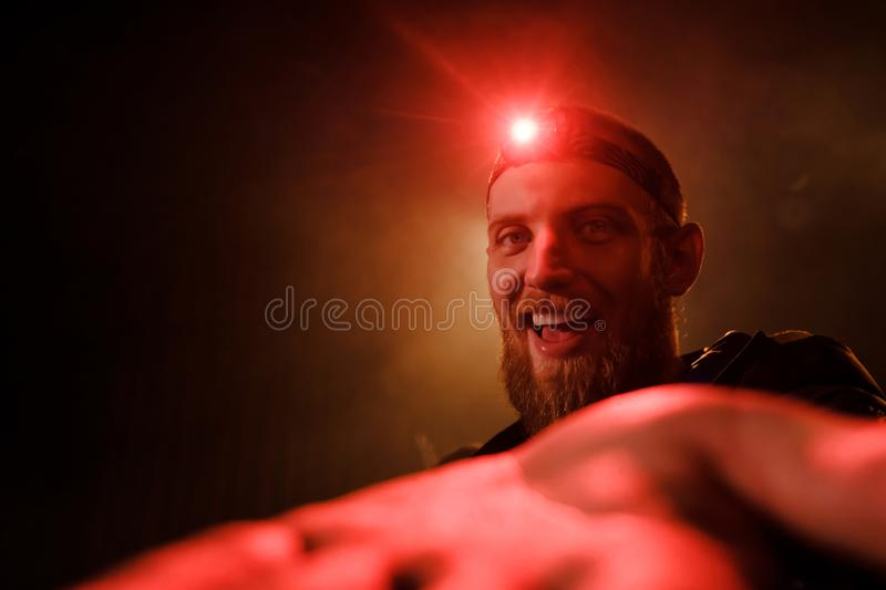 Close-up head-shot of young bearded extreme man with red head lamp on forehead. Close-up headshot of a brave young  bearded man with a red head light on his royalty free stock image