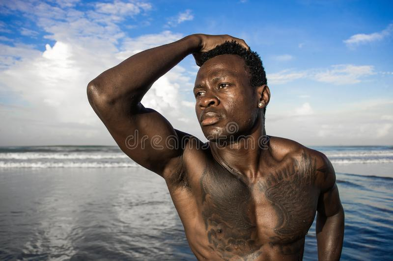 Portrait of young attractive and fit black African American man with strong muscular body posing cool model attitude on the beach royalty free stock photos