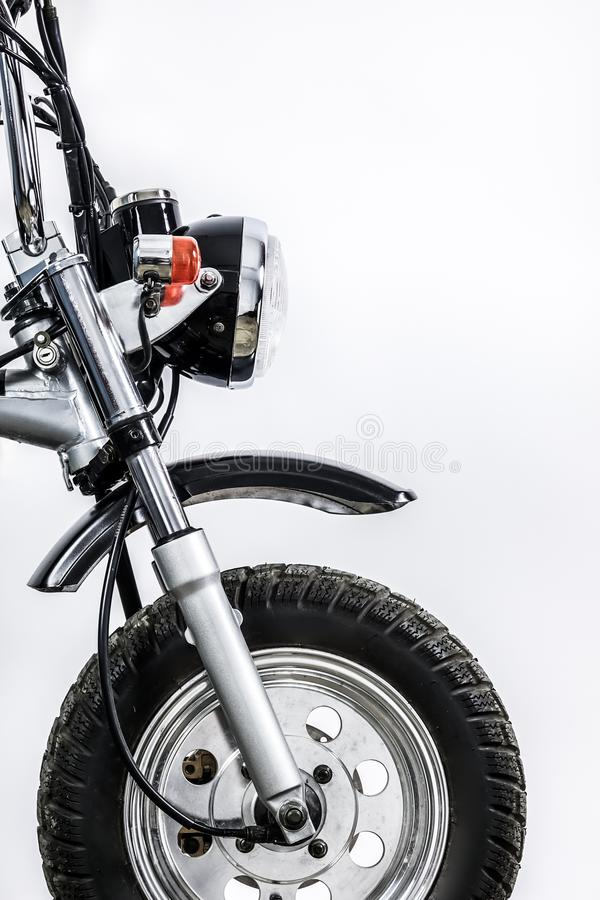Close up of headlight and front wheel on vintage motorcycle. Custom scrambler motocross. Retro motorbike on white background. Blank copy space for text royalty free stock image