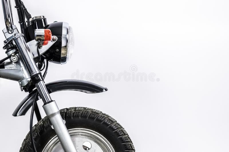 Close up of headlight and front wheel on vintage motorcycle. Custom scrambler motocross. Retro motorbike on white background. Blank copy space for text royalty free stock photo