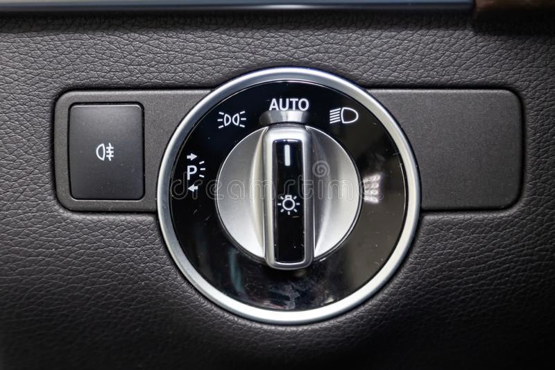 Close-up on the headlight switch control buttons and automatic adjust level dashboard in car in the back of a suv after cleaning. And detailing in the vehicle stock photo