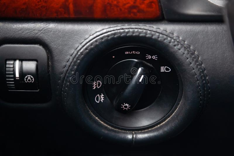 Close-up on the headlight switch control buttons and automatic adjust level dashboard in car in the back of a suv after cleaning. And detailing in the vehicle stock photos