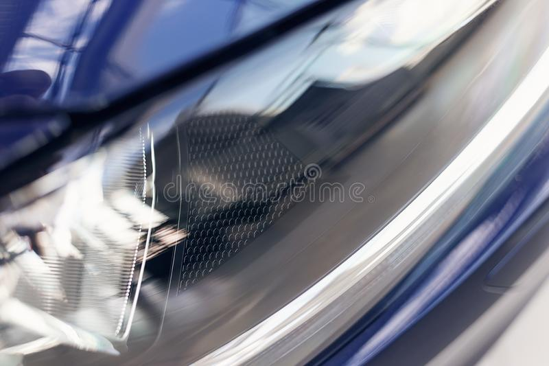 Close-up headlights of a modern blue color car. Detail on the front light of a car. Modern and expensive car concept stock photo