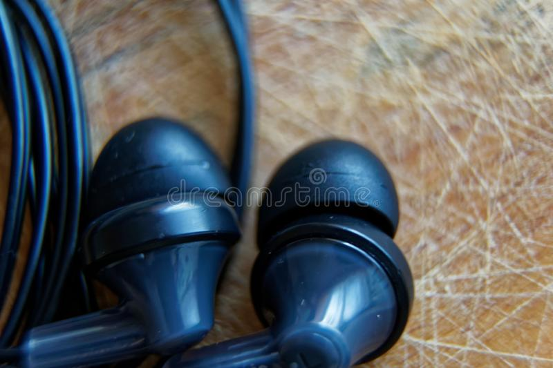 Close-up headphone stack on table, modern smartphone`s earbuds device accessories.  royalty free stock photo