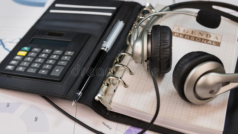 Close-up, headset lying on an organizer notepad. Call center table stock images