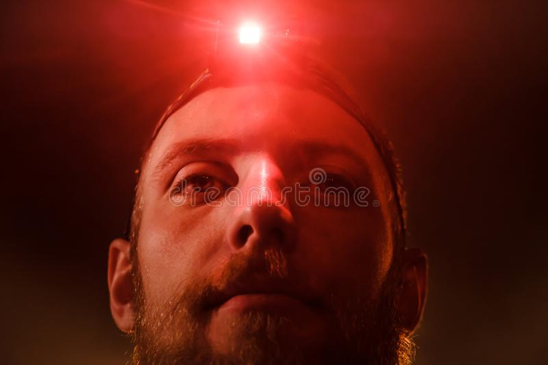 Close-up head-shot of young bearded extreme man with red head lamp on forehead. Close-up headshot of a brave young  bearded man with a red head light on his royalty free stock photo