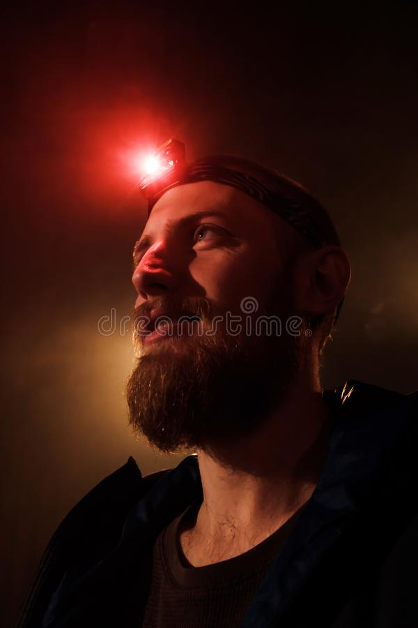 Close-up head-shot of young bearded extreme man with red head lamp on forehead. Close-up headshot of a brave young  bearded man with a red head light on his stock photography