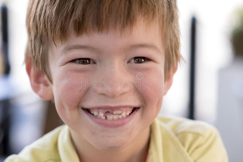 Close up headshot portrait of young little 7 or 8 years old boy with sweet funny teeth smiling happy and cheerful in joy face expr stock image