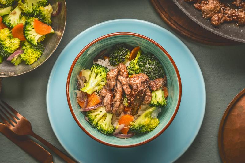 Close up of healthy balanced nutrition meal in bowl with beef meat, rice , steamed vegetables: broccoli and carrots served with pl royalty free stock photos