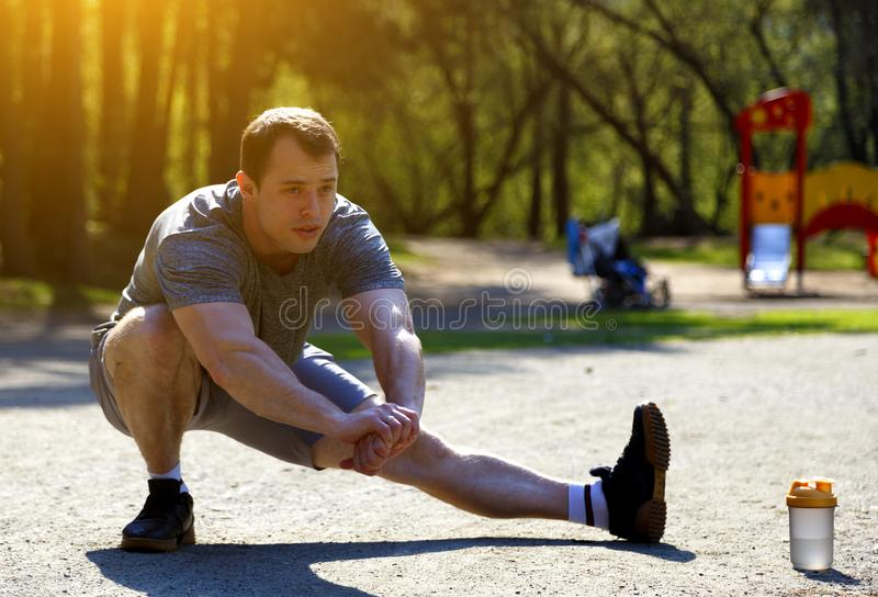 Close up healthy caucasian athlete stretching legs looking ahead royalty free stock photos