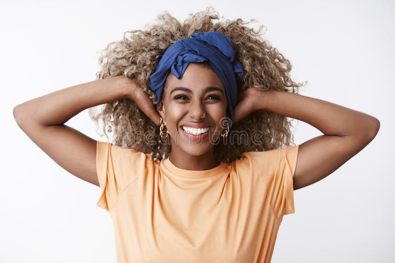 Close-up healthy and energized, enthusiastic attractive african-american curly-haired blond woman in headband, orange t. Shirt, stretching hands, hold hair and stock photo