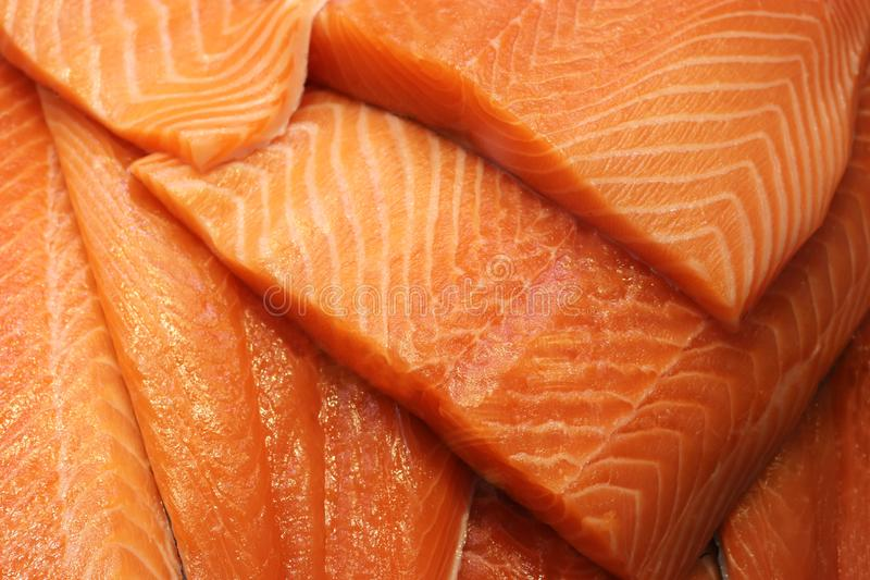 Close-up of fresh salmon fillets. Close-up of a heap of fresh and delicious salmon fillets, full frame stock photography