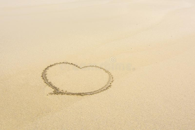 Heart drawn in the sand of a lonely beach stock image