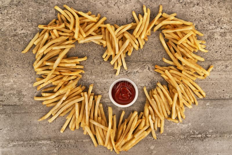 Close up on heart shape of french fries isolated on concrete background. Close up on heart shape of french fries isolated on concrete background, ketchup bowl royalty free stock photo