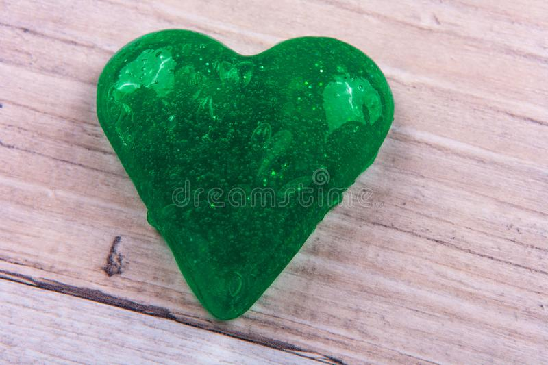 Close up of a heart shape green slime on a table.  royalty free stock photos