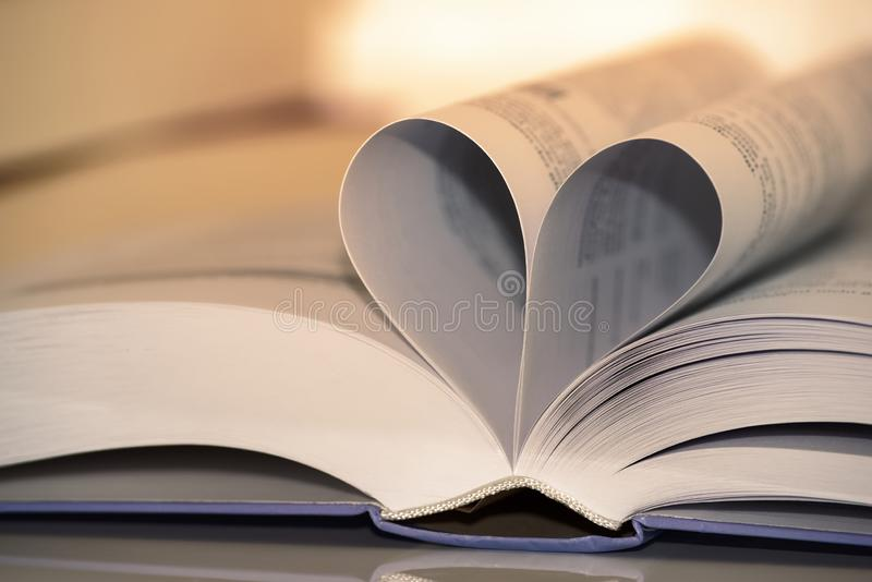 Heart shape from paper book against white background stock photo