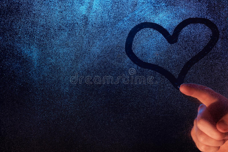 Close-up of heart shape symbol. On frozen window glass texture with man hand stock image