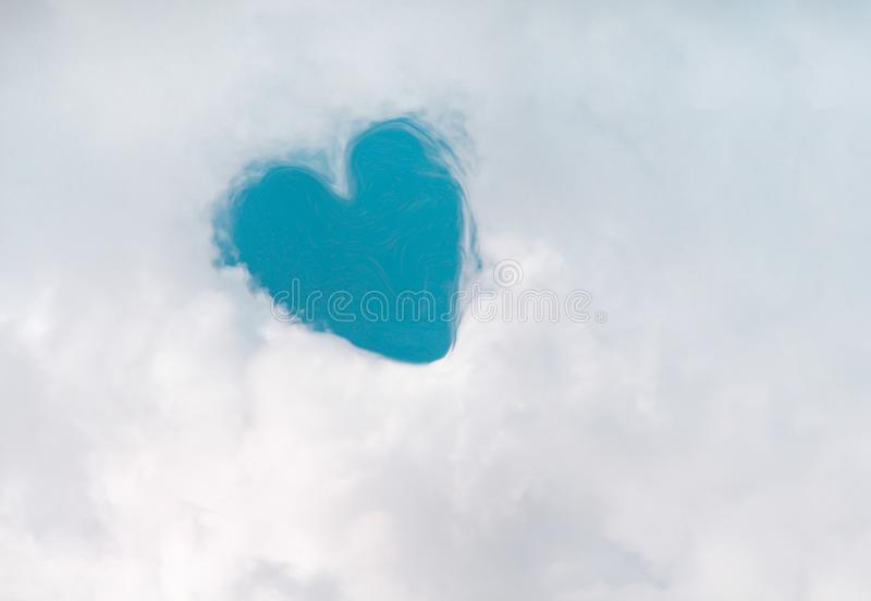 Heart shaped patterns in white fluffy clouds group on bright blue sky for background royalty free stock images