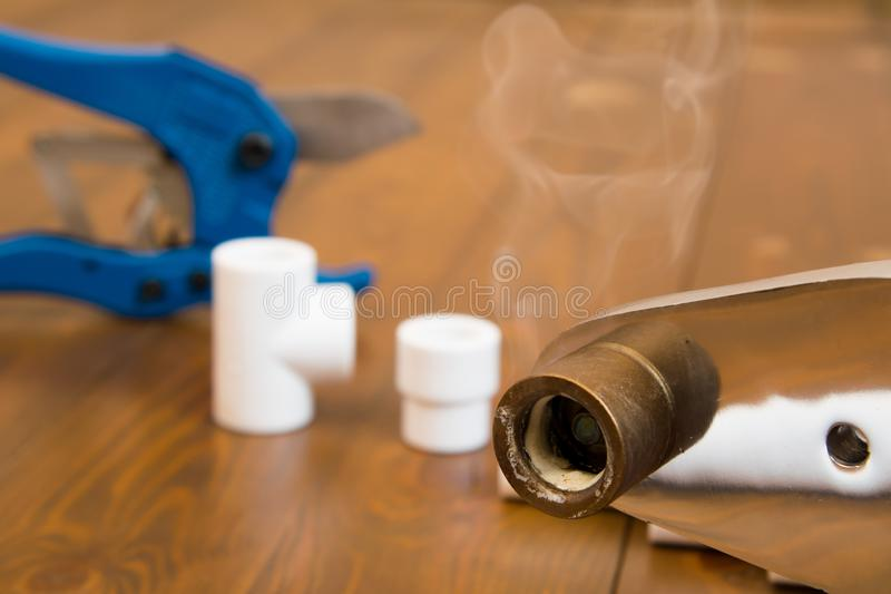 Close-up of a heated soldering iron with smoke from a melted plastic pipe, on a wooden background stock images