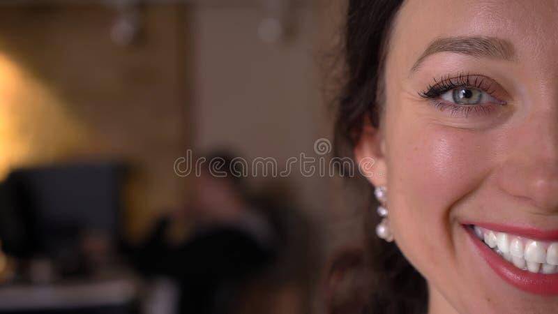 Close-up helft-gezicht spruit van het gezicht van de jonge vrij Kaukasische vrouw met ogen die recht camera met gezichts glimlach royalty-vrije stock afbeeldingen