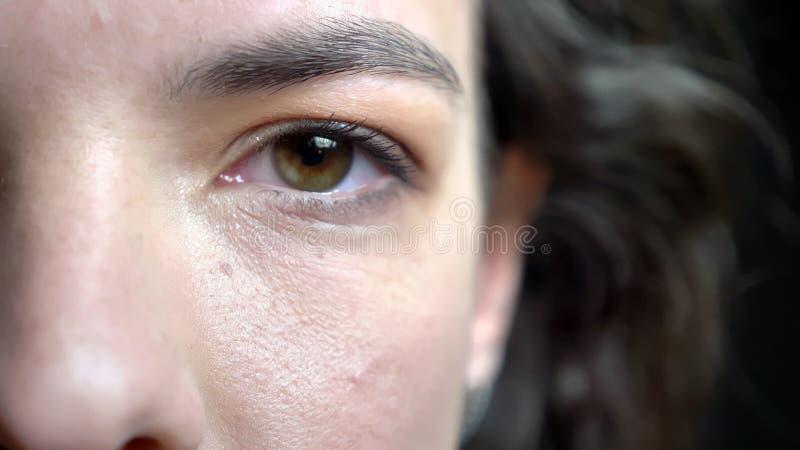 Close-up helft-gezicht spruit van jong vrij Kaukasisch vrouwelijk gezicht met donkerbruin krullend haar en bruin oog die recht be stock afbeeldingen