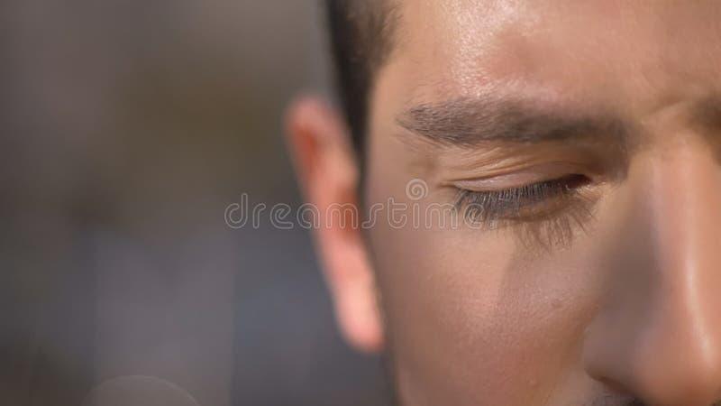 Close-up helft-portret van de Kaukasische mens met gesloten ogen op straatachtergrond stock foto's