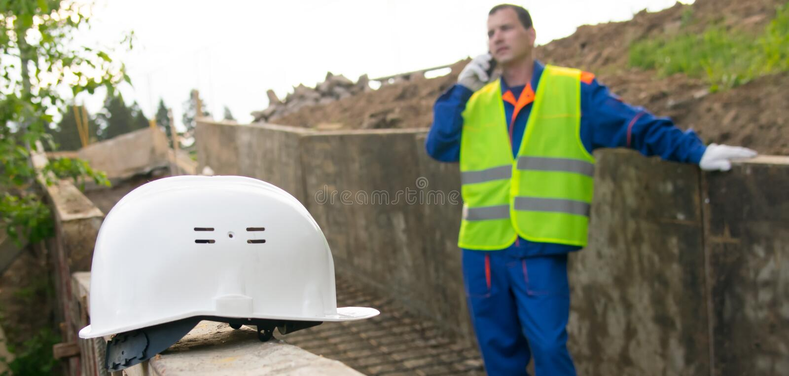 Close-up of the helmet, in the background, the engineer is talking on the phone with the sponsor about the construction of the stock image