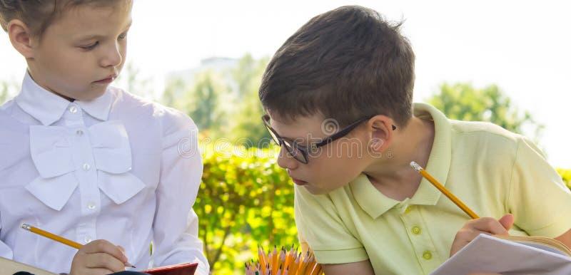 Close-up, in het park, in de verse lucht, de schoolkinderen thuiswerk het doen, een jongen en een meisje die piepen van elkaars b stock afbeelding
