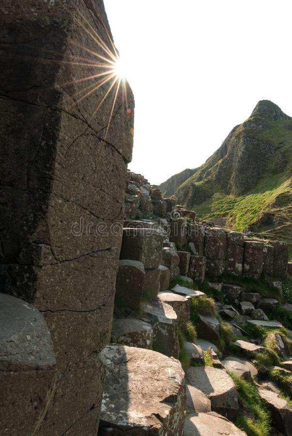 A close up of hexagonal stones at Giant`s Causeway with sun bursting over them. In a vertical composition stock photos