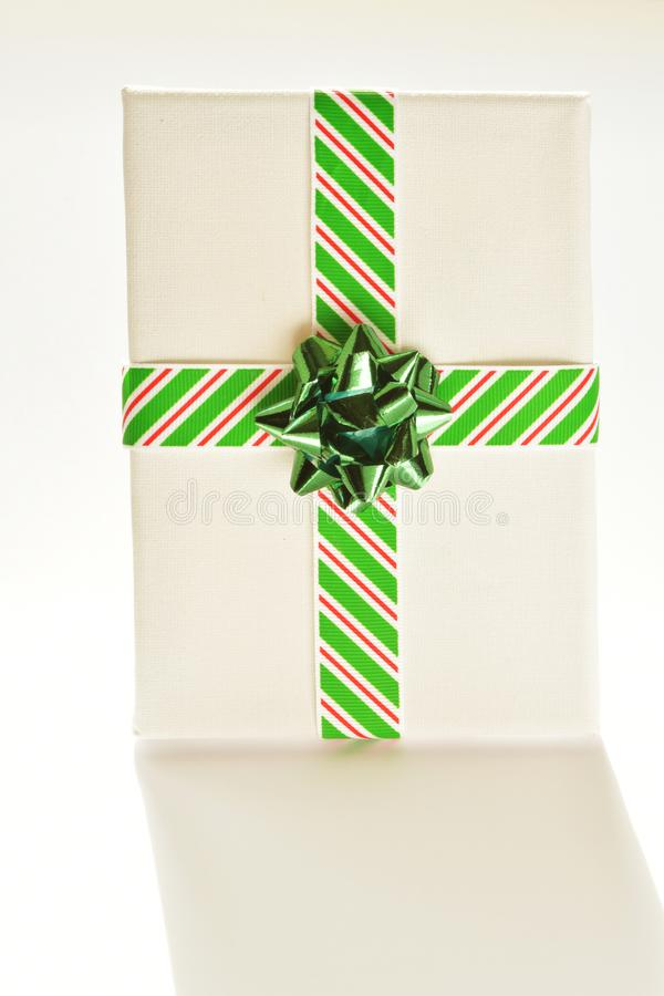 Close up of white canvas wrapped in Christmas ribbon, which is striped red, white and green, with green bow, on white. Close up high angle of white canvas stock photos