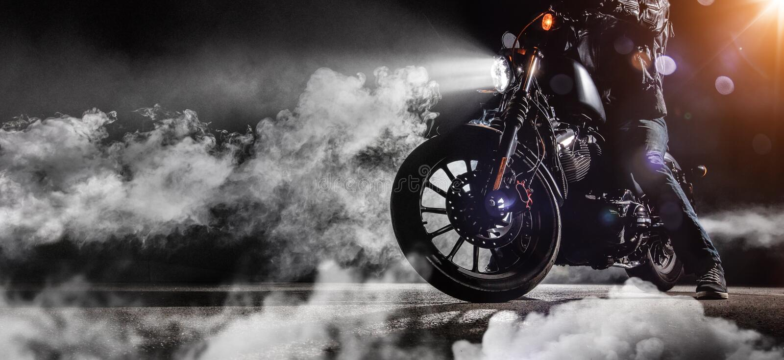 Close-up of high power motorcycle chopper with man rider at night. Fog with backlights on background royalty free stock photo