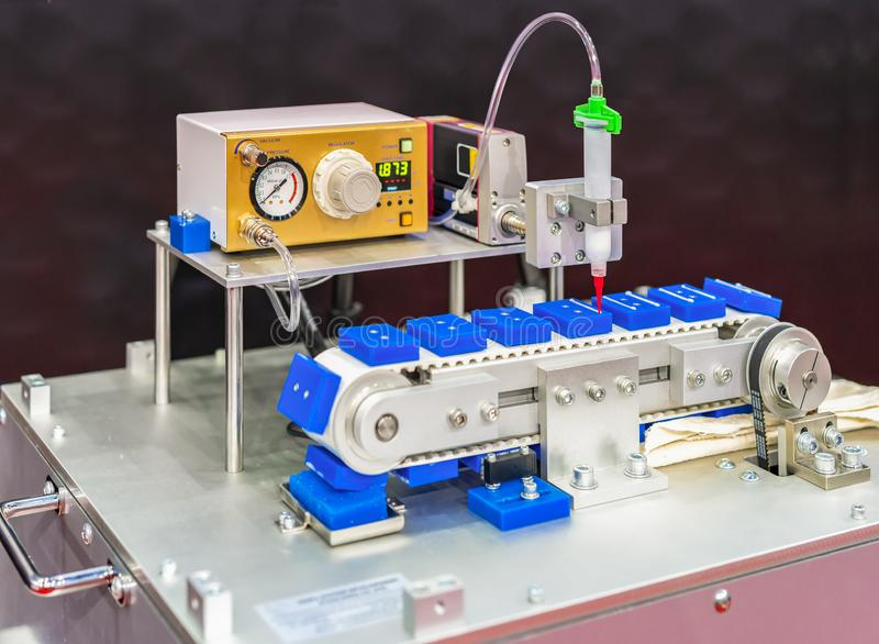 Close up High precision and technology of nozzle device and needle of automatic glue dispenser machine glue injection working on. Belt conveyor at factory royalty free stock image
