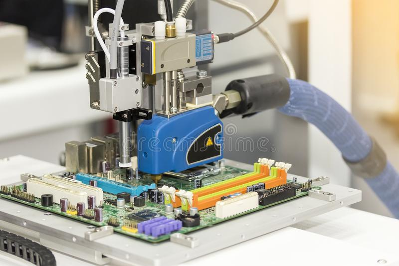 Close up High precision and technology of nozzle device and needle of automatic hot melt glue dispenser machine glue injection. Working on pcb in electronic royalty free stock photography