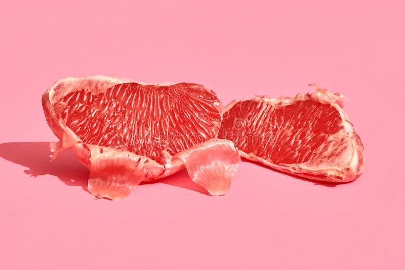Close up high quality image of peeled slices of juicy grapefruit on a pink background stock photo