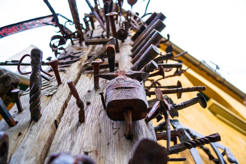 Close up of a high wooden pole Journeymen Pillar with iron/steel nails bolted in it, as a symbol of craftsmanship. royalty free stock photos
