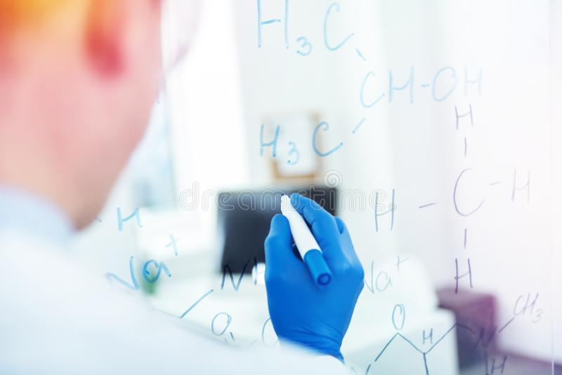 Close up of a highlighter being used for writing. Chemical formula. Close up of a highlighter being in a male hand while being used for writing a chemical stock images