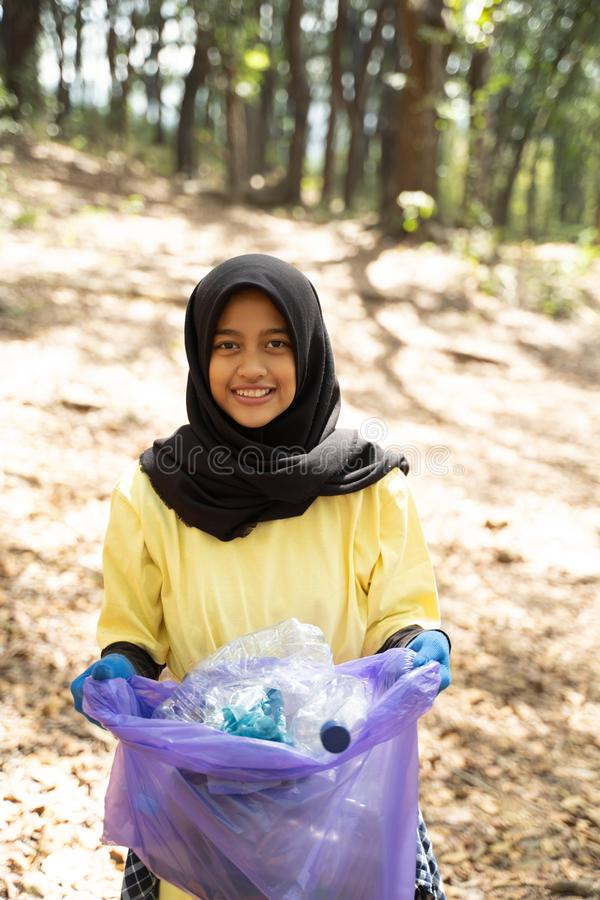 Close up of hijab woman smiling volunteer holding trash bag royalty free stock image