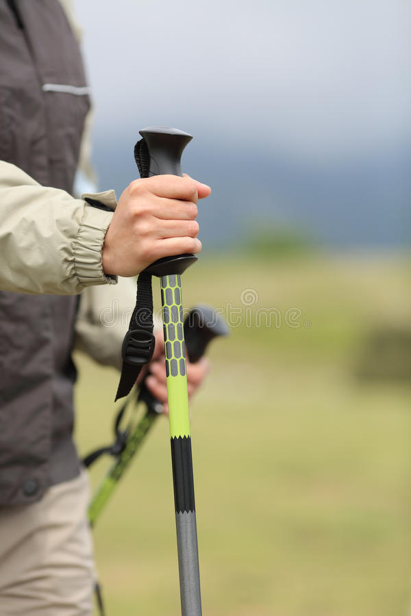 Close up of a hiker hands holding a hiking pole while walking. In the mountain royalty free stock image