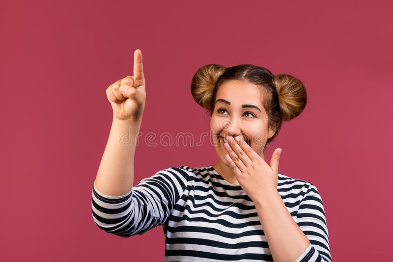 Close up of a hipster girl with funny hairstyle showing silence gesture isolated over pink background stock photo