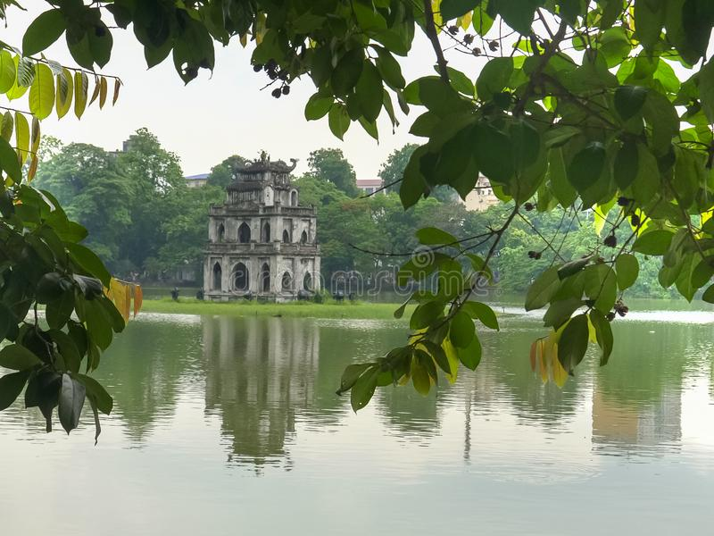 Close up hoan kiem lake and turtle tower framed by trees in hanoi royalty free stock photo