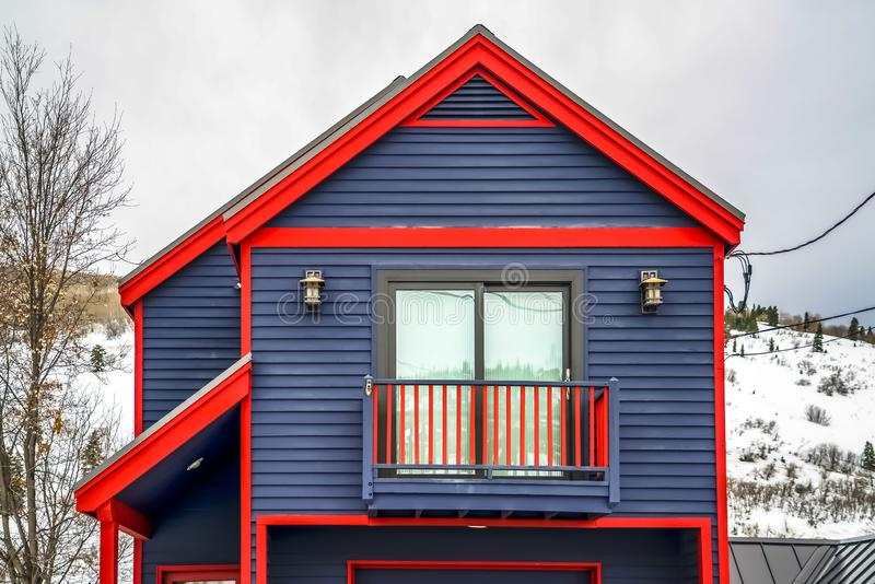Close up of home exterior with vibrant blue wall red frames and small balcony. Cloudy sky and mountain covered with snow in winter cna be seen in the royalty free stock image