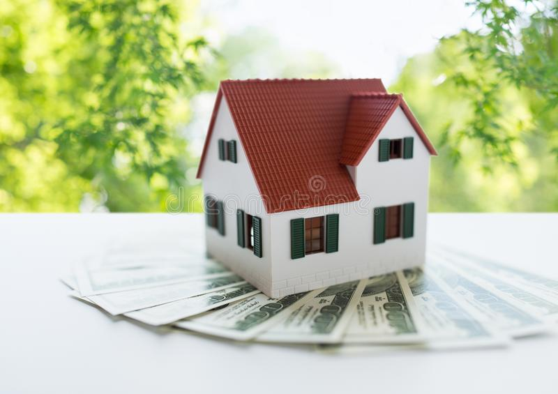 Close up of home or house model and money. Mortgage, real estate and property concept - close up of home or house model and money over green natural background stock photos