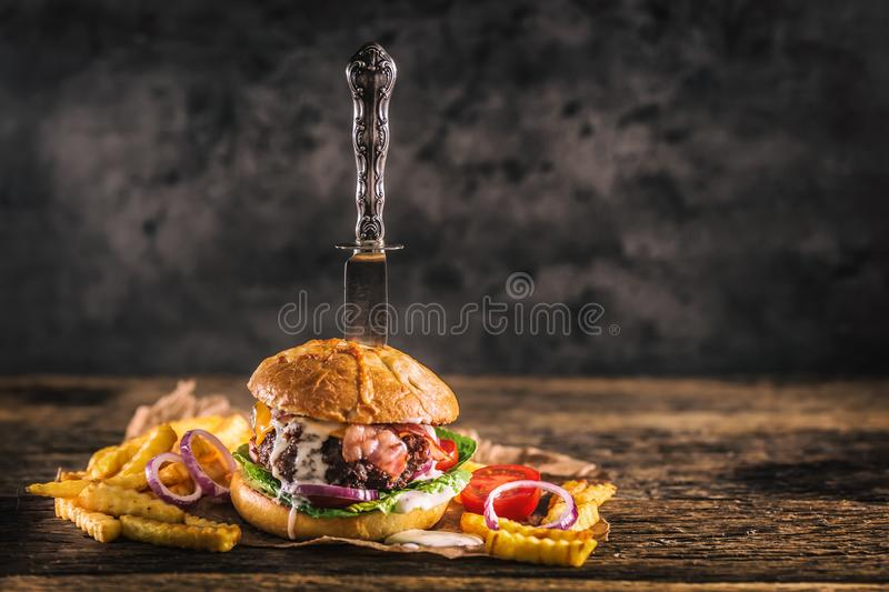Close-up home made beef burger with knife and fries on wooden ta. Ble stock photo