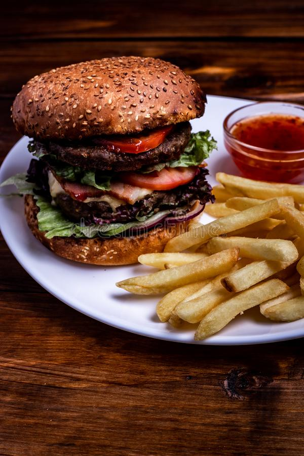 Close-up of home made burgers. bbq hamburger on the stone table with cheese and serrano ham royalty free stock photography