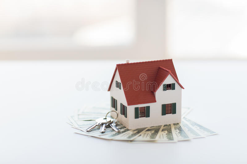 Close up of home model, money and house keys. Mortgage, investment, real estate and property concept - close up of home model, dollar money and house keys royalty free stock photos