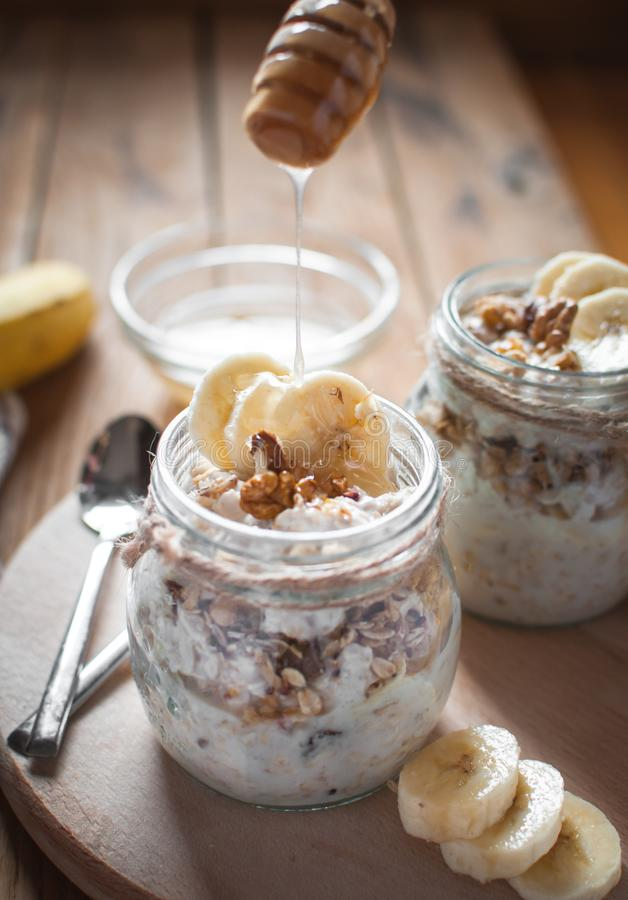 Close-up of homemade banana oats in a glass jar with honey dripping, on wooden background stock photography