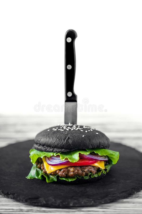 Close up of Homemade Black Burger with Cheese. Cheeseburger with royalty free stock photos